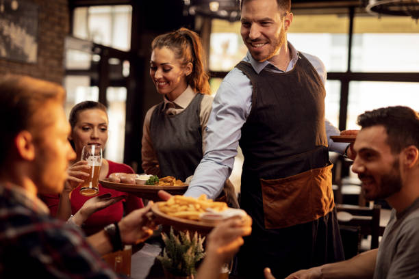 Young waiters serving lunch to group of friends in a pub. stock photo