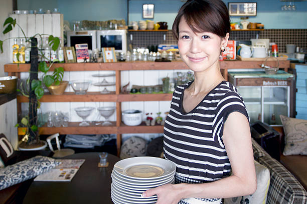 young waitress carring some of dishes in a restaurant - 吧 公共飲食地方 個照片及圖片檔
