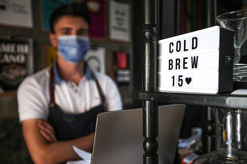 Young Waitress in Apron Sells Coffee and Cold Brew Coffee and Sosial Distancing