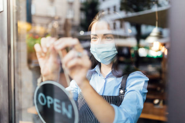 Young waitress opening a cafe stock photo