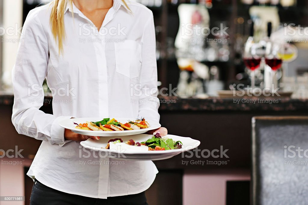 Young waitress serving food stock photo
