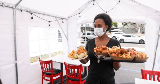 Young Waitress Serving Food to Customers in Outdoor Tent Wearing a Mask stock photo