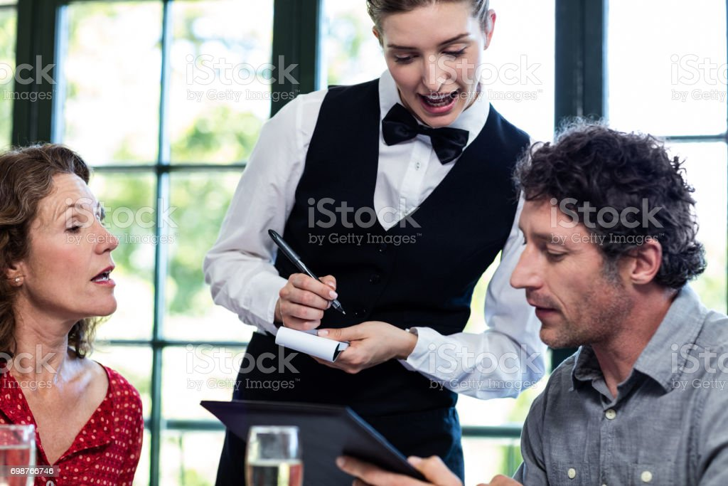 Young waitress taking an order from a couple stock photo