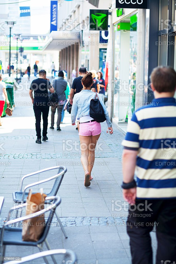 Young walking caucasian girl in pink shorts stock photo
