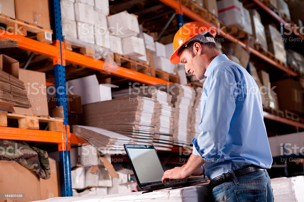 Young Warehouse Businessman with Laptop royalty-free stock photo