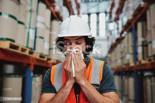 Sick caucasian workman sneezing and coughing covering mouth with handkerchief