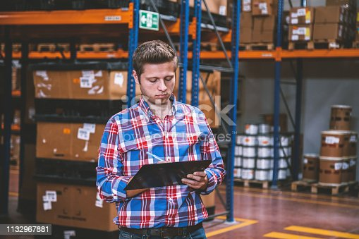 Portrait of an attractive young male warehouse worker or quality controller supervisor using a clipboard writing notes to take stock in a production hall at in distribution storage compartment