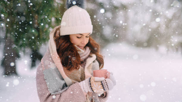 A young warmly dressed woman holds a cup of hot drink in her hands in a winter park. stock photo