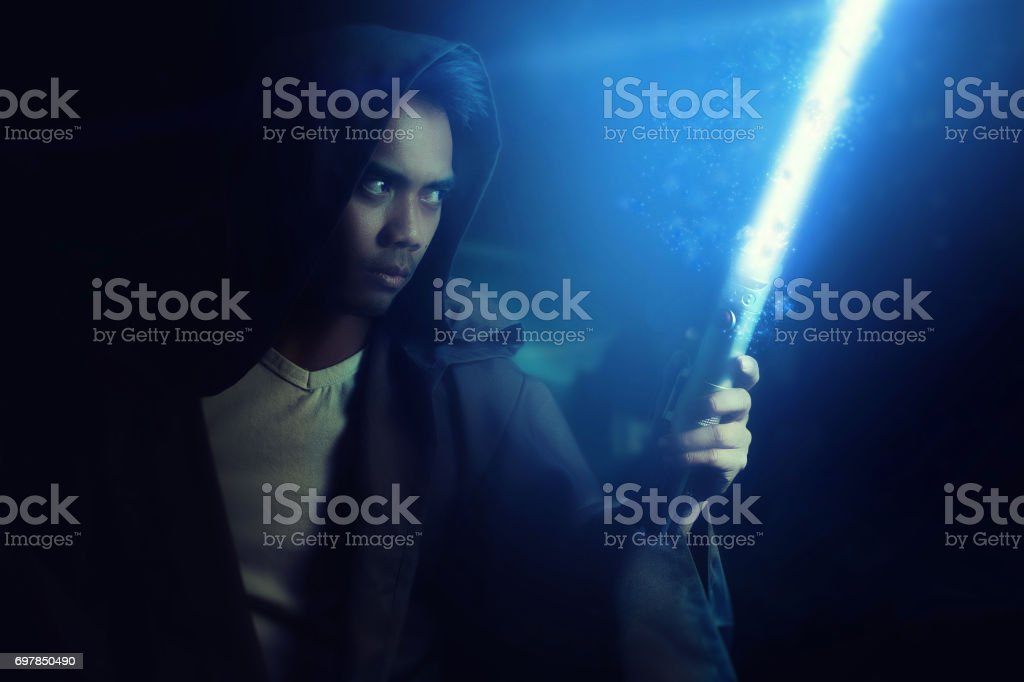 Young warrior holding a lightsaber Young warrior holding a lightsaber on a dark background Laser Sword Stock Photo