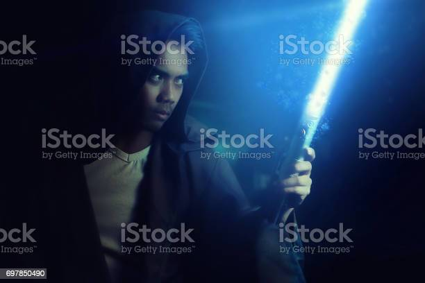 Young Warrior Holding A Lightsaber Stock Photo - Download Image Now