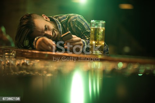 istock Young wasted man text messaging on cell phone while leaning on a bar counter. 672862138