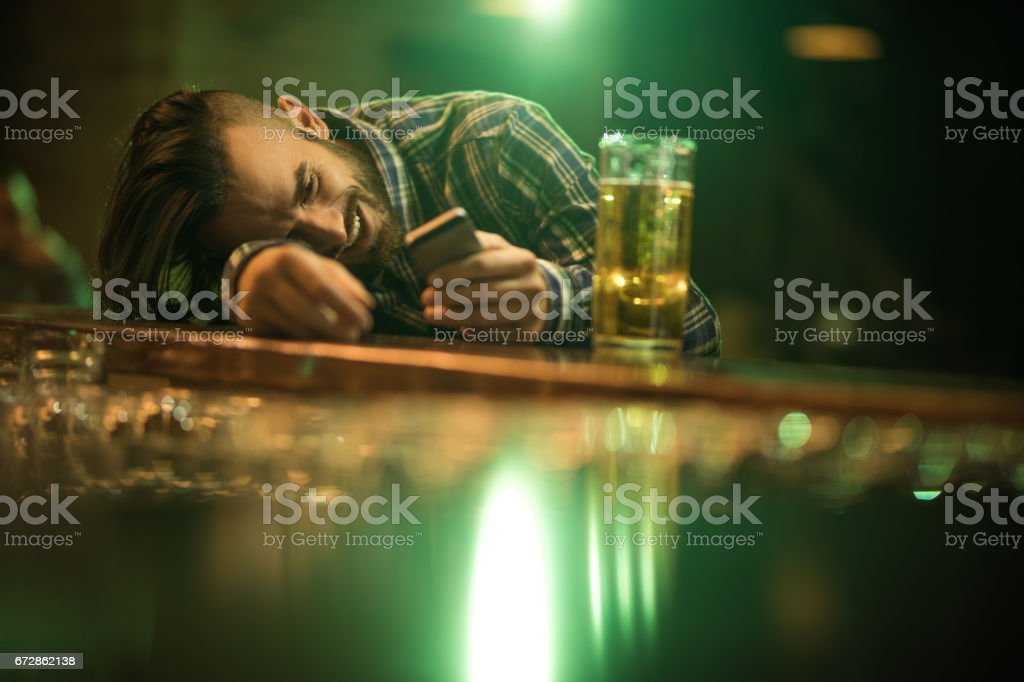 Young wasted man text messaging on cell phone while leaning on a bar counter. stock photo