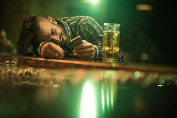 young wasted man text messaging on cell phone while leaning on a bar counter. - drunk stock photos and pictures
