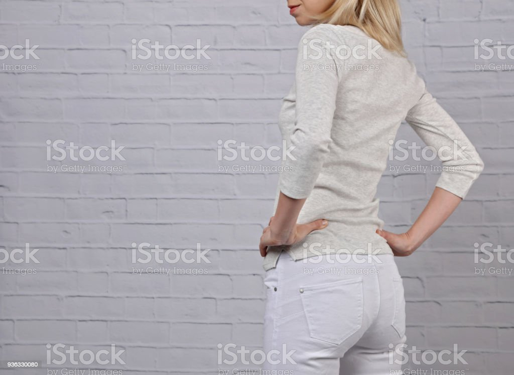 Young wearing woman in white pants close up. Perfect female body shape. White pants during period concept stock photo