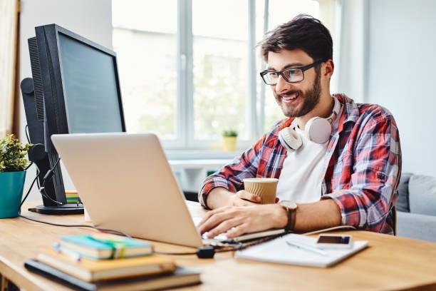Junger Webdesigner, der in seinem Home Office an Code arbeitet und Kaffee trinkt – Foto
