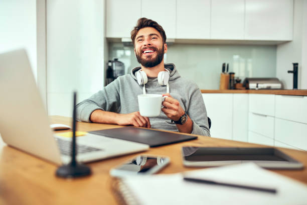 Young web developer laughing and drinking coffee while working from home office stock photo