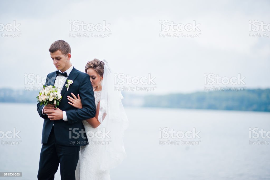 Young  wedding couple at the pier stock photo