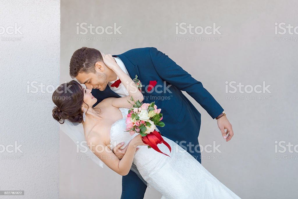 Young wedding couple kissing against a gray wall stock photo