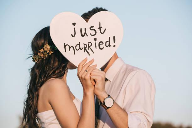 junge hochzeit paar küssen und hält herz mit frisch verheiratete inschrift - wedding stock-fotos und bilder