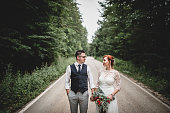 Young happy wedding couple walking on the road through the forest