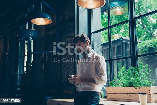 istock Young well dressed entrepreneur is browsing on his mobile phone at the modern office, behind is a window, he is focused and serious 936437560