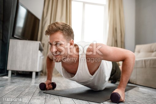 Young well-built man go in for sports in apartment. Strong muscular guy stand in plank position using dumbbells and look forward. He use all his strenghts