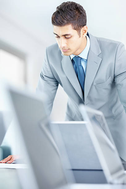 Young well-dressed businessman looking in laptop stock photo