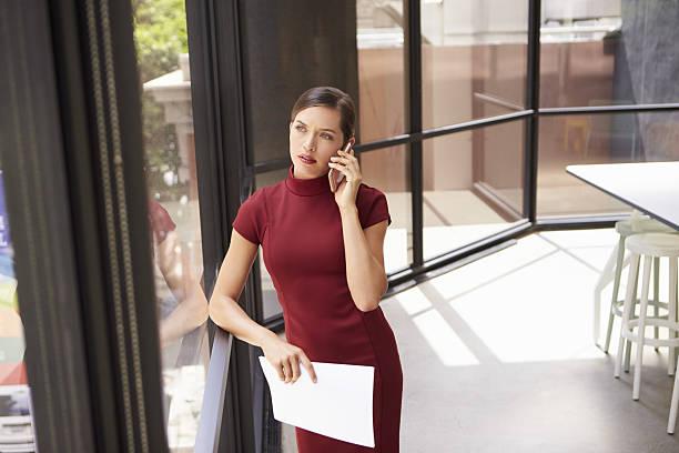 young white businesswoman on phone looking out office window - enge kleider stock-fotos und bilder