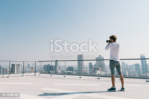 istock Young white Caucasian man taking cityscape photo on building rooftop on sunny day. Photography hobby, gadget technology, or leisure activity concept. With copy space on blue sky 911538182