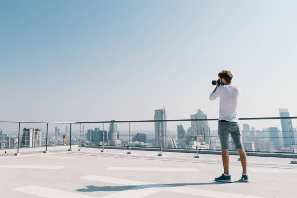 Young white caucasian man taking cityscape photo on building rooftop picture id911538182?b=1&k=6&m=911538182&s=612x612&w=0&h=hdiec gm15iim 0ck1h7t q5grhxodhazsrue56ulwg=