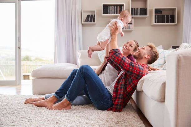 Young white couple play with their toddler in sitting room stock photo