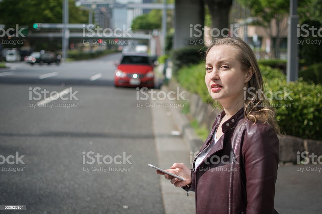 Young White Female Waiting For Taxi stock photo