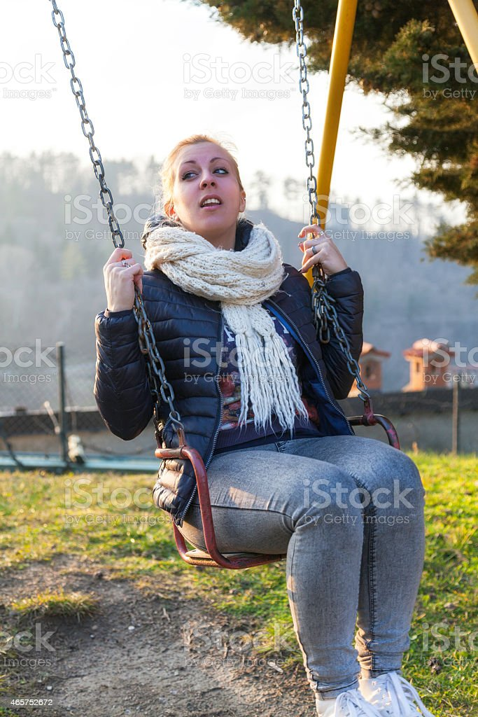 Young white girl play on a swing. Color image stock photo