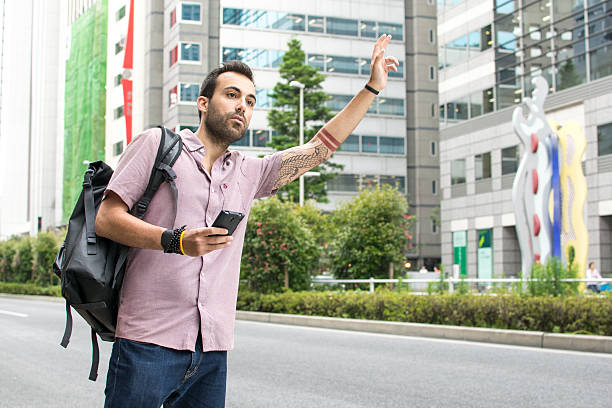 young white man holding a cellphone hailing uber taxi - rideshare stock photos and pictures