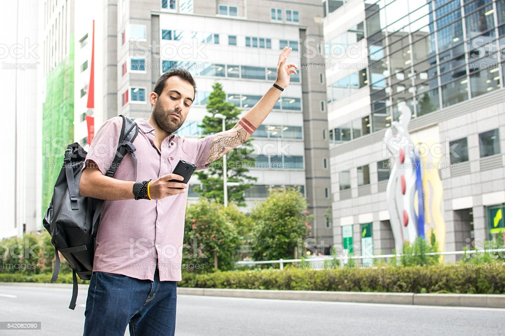 Young White Man Holding A Cellphone Hailing Uber Taxi stock photo