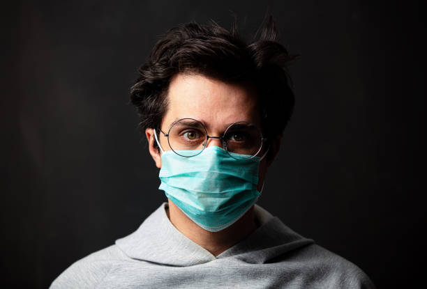 young white man in glasses and protective mask stock photo