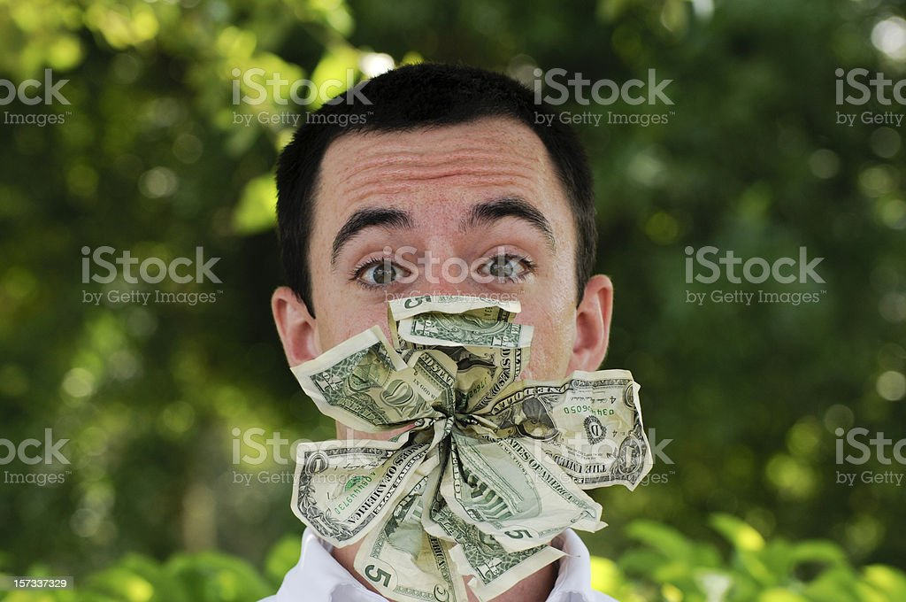 Young White Man With Wad of Money in his Mouth stock photo