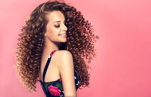 Young, wide smiling brown haired woman with voluminous hairstyle in profile. Young, wide smiling brown haired woman with voluminous hairstyle in profile. Beautiful model with long, dense, curly hairstyle and vivid makeup. Dense, spring-like,elastic curls in a hairstyle of young, pretty model. Frizzy hair. curly hair stock pictures, royalty-free photos & images