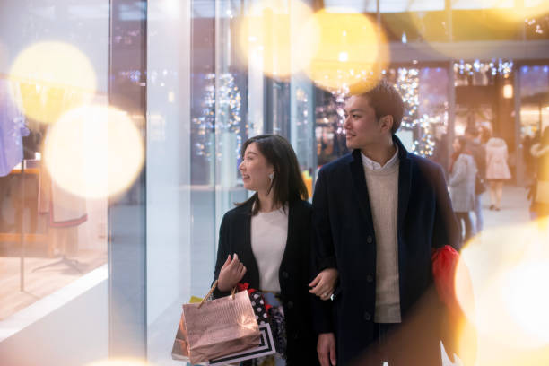 Young wife and husband shopping together at Christmas night Young wife and husband shopping together at Christmas night shopping couple asian stock pictures, royalty-free photos & images