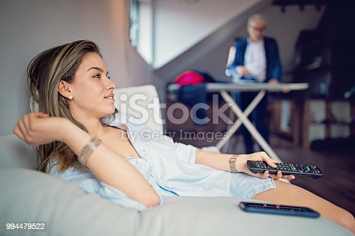 802472024istockphoto Young wife is looking TV till her husband is ironing the laundry 994479522