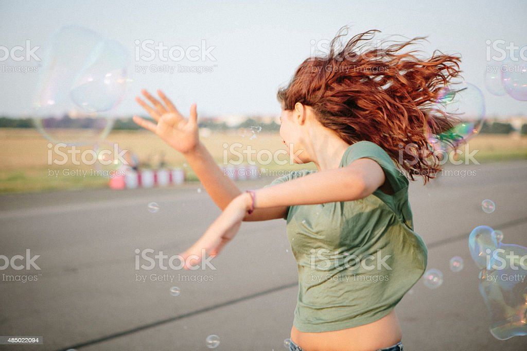 young wild woman fighting against soap bubbles wall stock photo