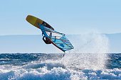 Windsurfer riding waves and jumping