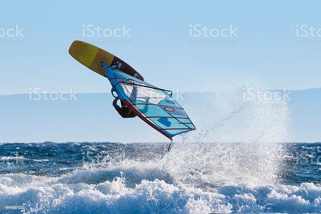 Young Windsurfer Jumping Wave on Windsurf Board stock photo