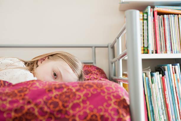 junge wehmütige girl lying on bed - etagenbett weiss stock-fotos und bilder