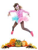Beautiful teen girl in pink witch costume and halloween makeup jumping over carved pumpkin monsters. Isolated on white