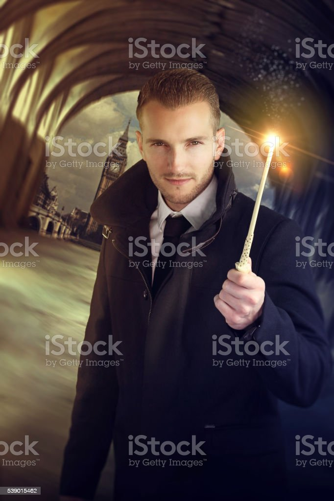 young wizard holding a magic wand stock photo
