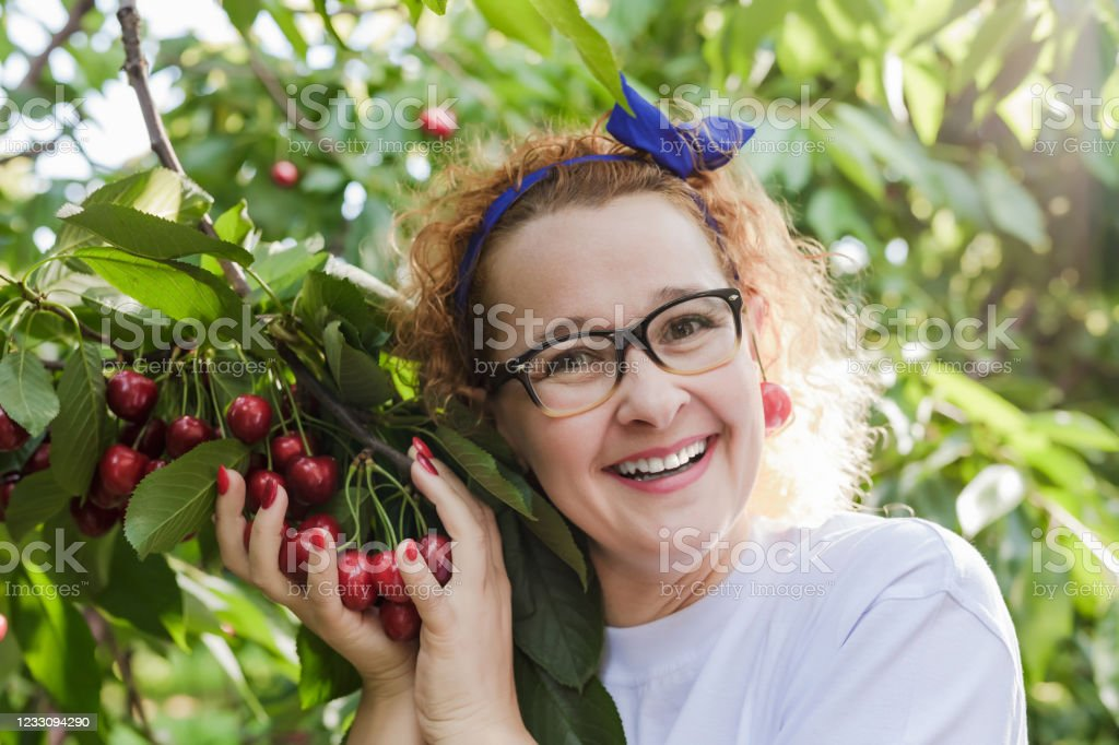 Young woman - 40-45 years with a cherries Smiling young teenage girl in her 15-18 years picking cherries in the cherry garden, close-up Adult Stock Photo