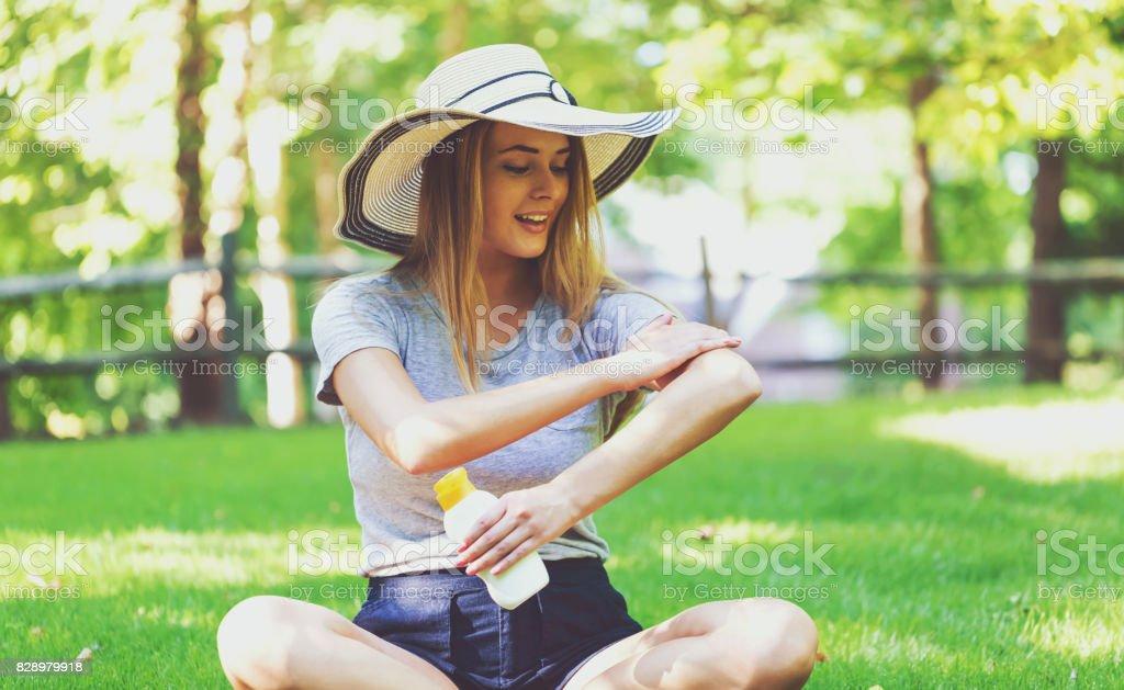 Junge Frau eine Flasche Sonnencreme außerhalb – Foto