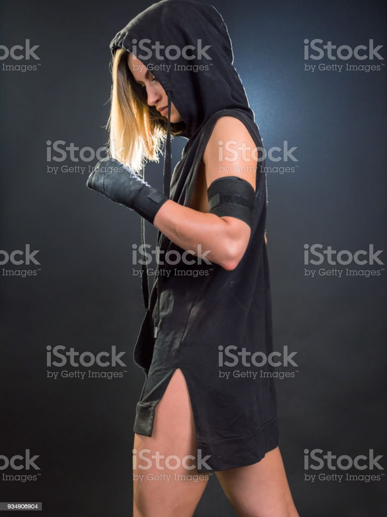 Young woman a kickboxer wearing a hooded shirt posing in fighting stance stock photo
