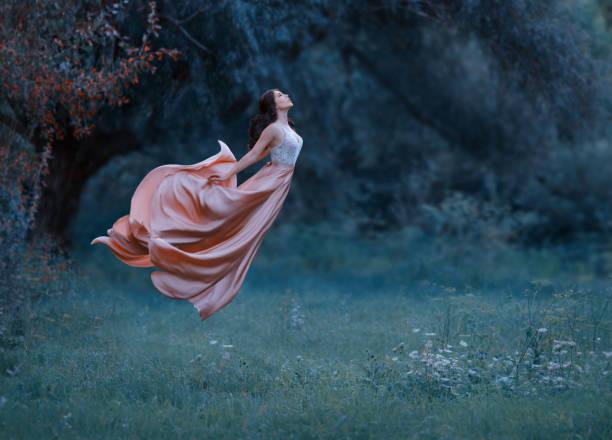 eine junge frau, eine geheimnisvolle hexe wie ein schmetterling in der luft schwebt. eine luxuriöse, langen kleid, im wind wehende. kalten wald hintergrund. verzauberte prinzessin. kunstfoto der levitation - gothic kleid stock-fotos und bilder